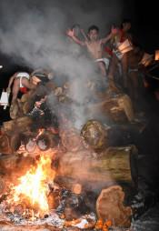 燃え盛る歳戸木に登り、気勢を上げる男衆