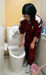 改修された洋式トイレを掃除する生徒。県内では学校トイレの洋式化が加速しそうだ=雫石町・雫石中