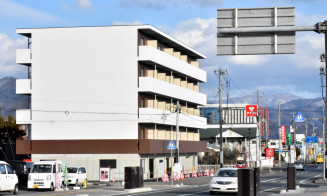 新しい岩手医大付属病院の近くに建てられているマンション(手前左)。9月の開院を見据えて集合住宅の建設が相次いでいる=21日、矢巾町又兵エ新田