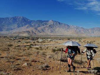 広大な砂漠地帯を進む。強烈な日差しから身を守るため、日傘を差すハイカーも多くいた