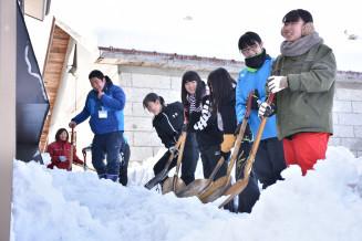 家を覆うように積もった雪を取り除く宮古水産高の生徒ら