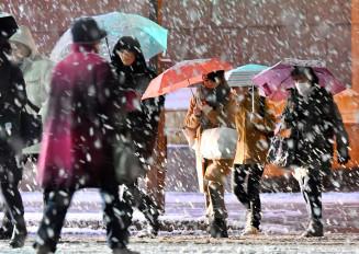 久々の積雪でぬかるむ足元に気を付け、傘を差して家路を急ぐ市民ら=23日午後5時22分、盛岡市中央通