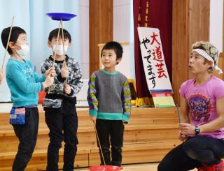 本県沿岸を駆け抜ける「縦走」の壮行会で、子どもたちに皿回しを教えるジロー今村さん(右)