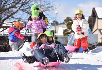 雪の滑り台で遊び、歓声を上げる園児