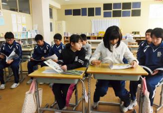 一人一人絵本を手に取り、商船漂流の歴史を学ぶ児童