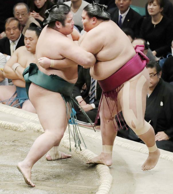 錦木(左)がきめ出しで御嶽海を破る