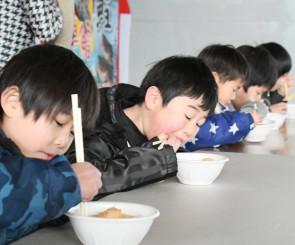 たら汁早食い競争でコロッケや野菜を懸命に食べる子どもたち