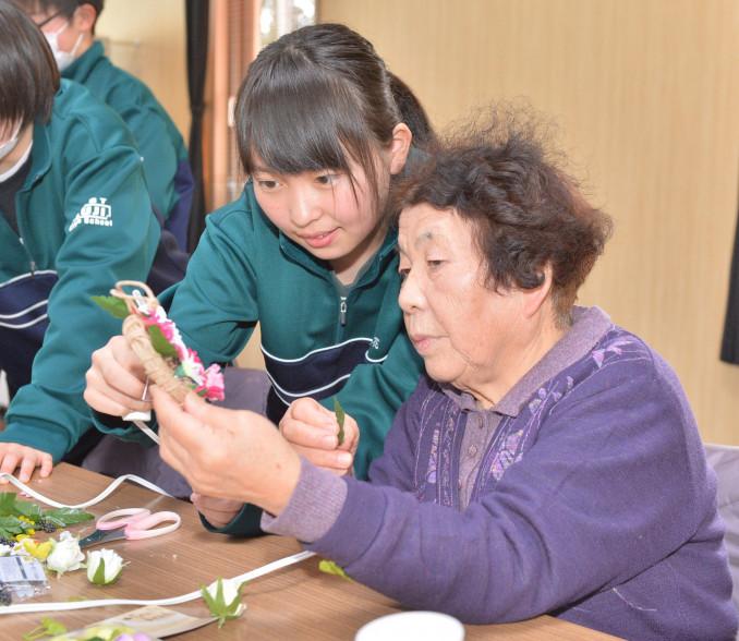 住民とリース作りを楽しむ久慈東高の生徒