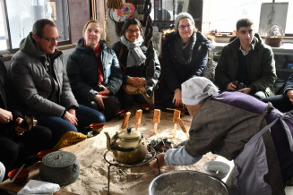 いろりを囲み、山村の暮らしを体験する外国人