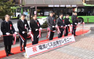 県交通が新たに導入した電気バスを背にテープカットで運行開始を祝う関係者