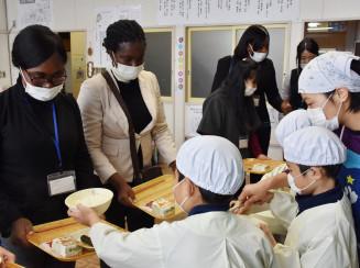児童に配膳してもらい日本の給食システムを学ぶ研修生