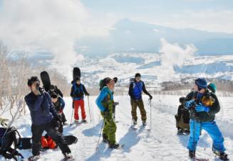 雪上車ツアーの参加者に雪山での注意点や危険箇所などを伝えるガイドの高橋孝精さん(中央)=1月13日、八幡平市・大黒森付近