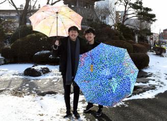 障害者アートを基調にしたブランド「MUKU」の傘を手に「福祉と楽しく出合う場を提供したい」と語る松田文登さん(左)、双子の弟・崇弥さん