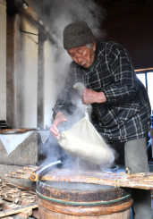 湯気が立ち上る作業小屋で、昔ながらの豆腐作りに励む佐藤モモエさん=4日、陸前高田市矢作町
