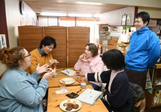 商品を試食し、外国人に好まれそうな食感や味を従業員(右)に伝えるALT