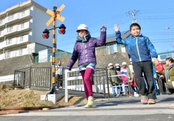 8年ぶりに列車が通る踏切を安全を確認して渡る磯鶏小の児童=5日、宮古市上村
