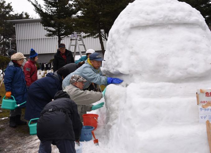 雪像制作に取り組む盛岡ふるさとガイドの会のメンバー=6日、盛岡市内丸
