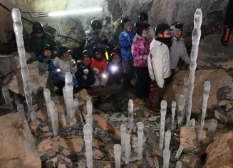 洞窟内で輝く氷筍。美しい眺めに山形小の児童が歓声を上げる=8日、久慈市山形町・内間木洞
