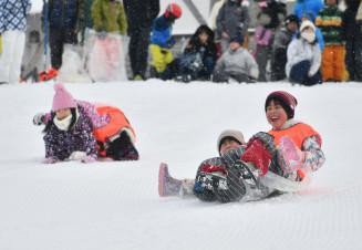 ビニールの袋で雪の斜面を滑り降りる子どもたち