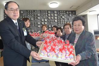 民部田政彦健康福祉課長に安産祈願の「おっほ人形」を手渡す山崎カツさん(右)ら