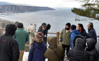 黒崎展望台から、なだらかに広がる海成段丘(奥)を見る参加者ら=13日、普代村