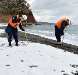 雪が積もった海岸で行方不明者の手掛かりを探す岩泉署員