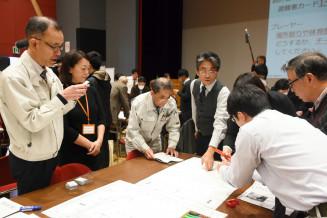 指導員のアドバイスを受け避難所運営ゲームに取り組む参加者