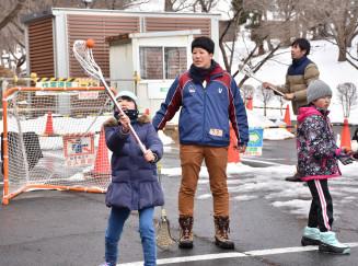 深津咲奈さん(左から2人目)に教わりながらラクロスを体験する子どもたち