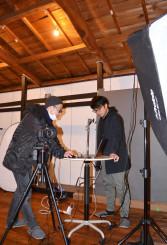 太い梁に倉庫の面影を残す、貸し撮影スタジオ「nido」でオープンに向け準備を進める伊藤治郎さん(右)