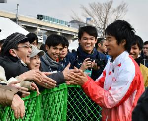 5連覇で世界選手権出場を決め、ファンと喜び合う高橋英輝選手(右)=17日、神戸市・六甲アイランド甲南大周辺