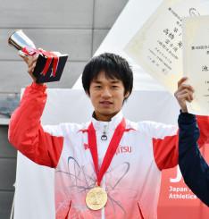 男子で5連覇を達成し、表彰式でトロフィーを掲げる高橋英輝