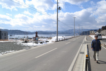 【2019年2月13日】 海抜14.5メートル以上にかさ上げ整備された県道吉里吉里釜石線。中央左に灯台の形をした震災記念碑、左奥に蓬莱島が見える