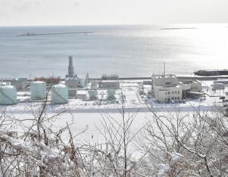 【2019年2月8日】 久慈国家石油備蓄基地(手前)の東沖合では、湾口防波堤の整備がだいぶ進んだ
