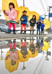 小雨の中、傘を差して歩くつなぎ幼稚園の園児。雪解けが進み、春の気配が漂う=20日、盛岡市繋