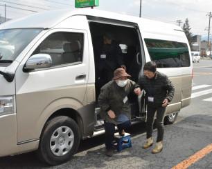 試験運行が始まった「おでかけバス」を利用する高齢者。地域のボランティアが支える