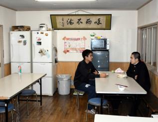 寮訓の「和而不流」が掲げられた食堂で語り合う寮生。かつては40人近くが寄宿したが、現在は7人で協力しながら運営している