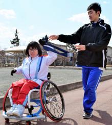 2区走者の久保寿瑳さん(右)からたすきを受ける練習をする3区走者の安倍百香さん