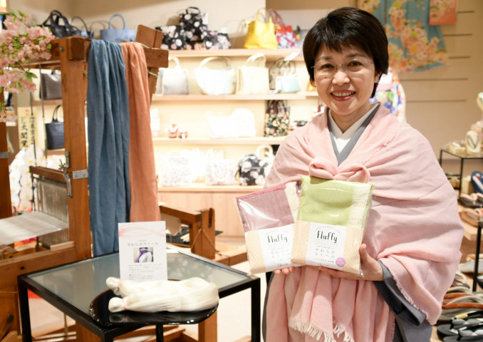 総本店の開店を機に発売した県南産の生糸を使ったストールを身に着ける従業員