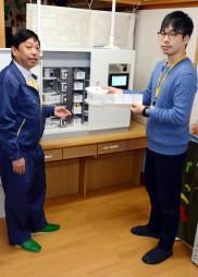 配薬支援装置で負担軽減を体験する佐々木昂平ケアマネジャー(右)と高橋武・開発グループリーダー
