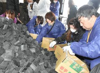 木炭の詰め込み作業を体験する参加者