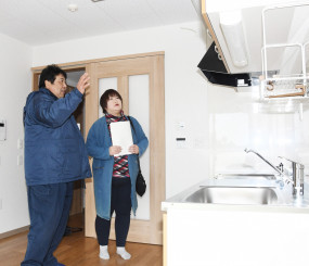 施工業者から部屋の設備について説明を受ける入居内定者(右)