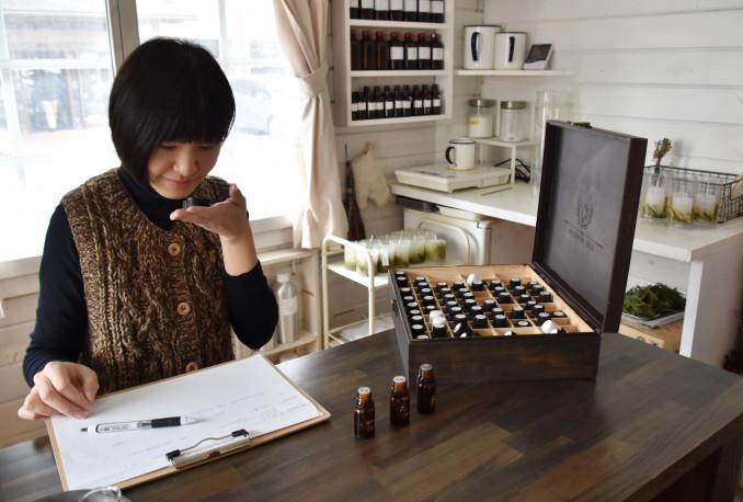 アロマオイルの瓶のふたを手に取り、香りの組み合わせを確かめる佐々木香織さん