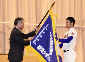 赤坂昌吉校長から選抜旗を受け取る及川温大主将(右)=盛岡市・盛岡大付高