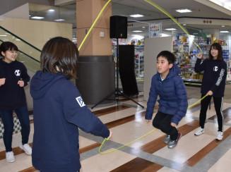 学生の手ほどきを受けてダブルダッチに挑戦する児童