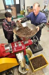 ツバキの実を搾油機に入れてつばき油を作る石川秀一さん(右)と春枝さん夫妻=4日、陸前高田市竹駒町・石川製油