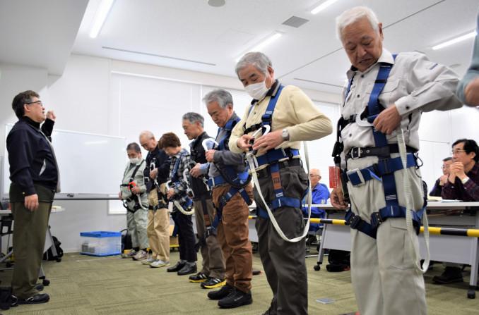 高所作業中の転落を防ぐため、装備の付け方を確認する参加者