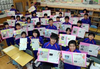 生き方や将来の夢をまとめた「大槌希望新聞」を手に笑顔をみせる大槌学園6年1組の児童