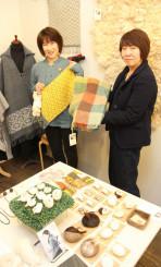 ストールや小物が並ぶ会場。水野ひろ子さん(右)と木村加容子さんは「県産羊毛の可能性を知ってほしい」と来場を呼び掛ける