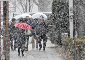 雪が強まり、視界が白く覆われた盛岡市。傘を差して歩く姿も目立った=7日午後3時23分、同市内丸