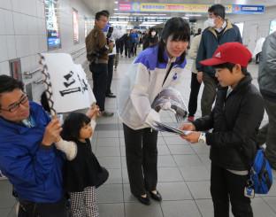 2018年3月11日。JR静岡駅そばで復興状況を伝える号外を配布する岩手日報社の社員
